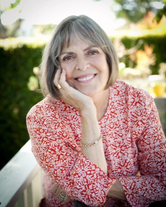a white woman with silver hair wearing a red and white patterned shirt