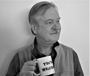 a white male with a mustache holds a coffee mug