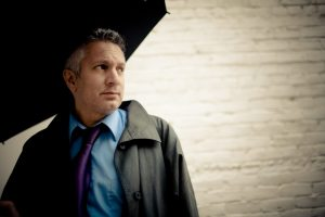 a chicano man wearing a teal button-down shirt, purple tie, and olive raincoat holds an umbrella