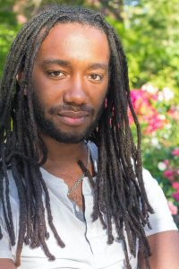 a black male with dreadlocks wearing a white shirt with flowers in the background