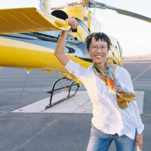 an Indonesian-Chinese-American woman wearing a white shirt and blue jeans places a hand on a yellow helicopter