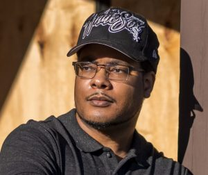 a black man with glasses, gray polo, and Chicago White Sox hat