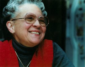A Dominican woman with silver hair, glasses, black turtleneck, and red vest
